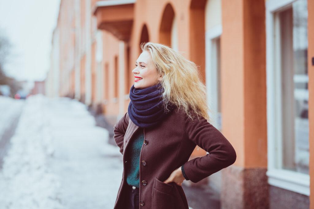 Kuvassa Amanda Pasanen seisoo lumisella kadulla ja hymyilee aurinkoisesti.