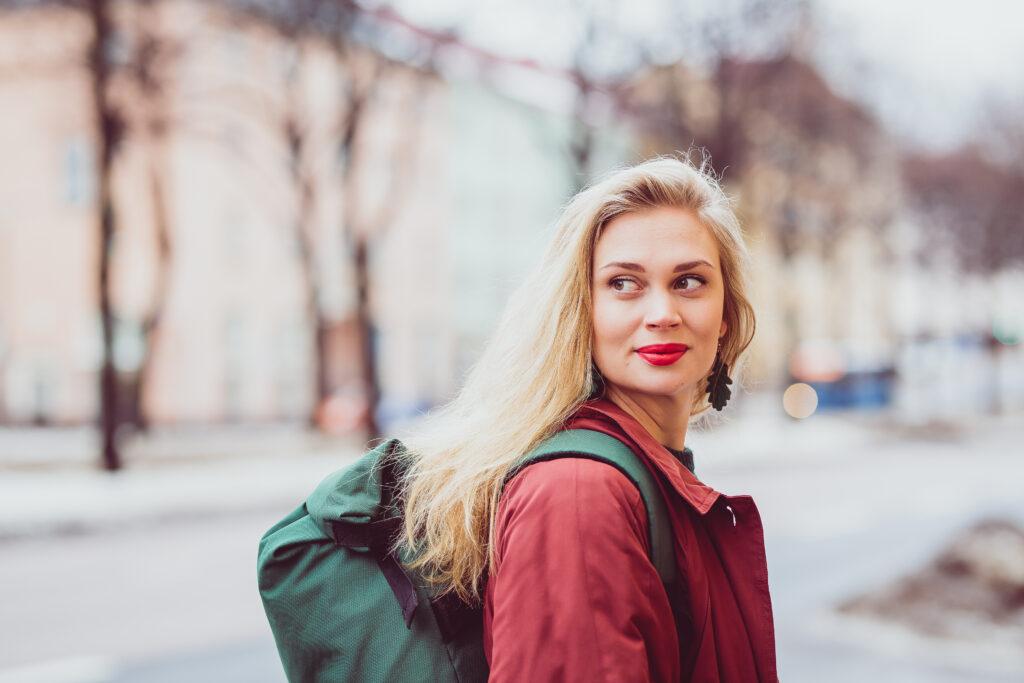 Kuvassa Amanda Pasanen seisooo kadulla punaisessa takissa ja vihreä reppu selässä. Hän katsoo olkansa yli ohi kameran. Taustalla värikkäitä kerrostaloja.